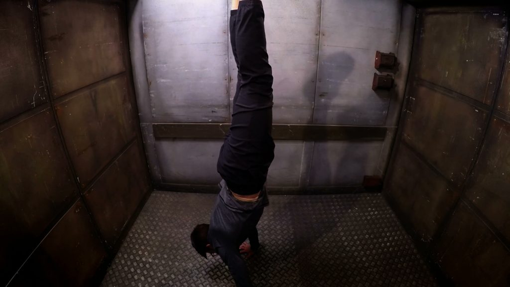 Louis doing a handstand in the lift.