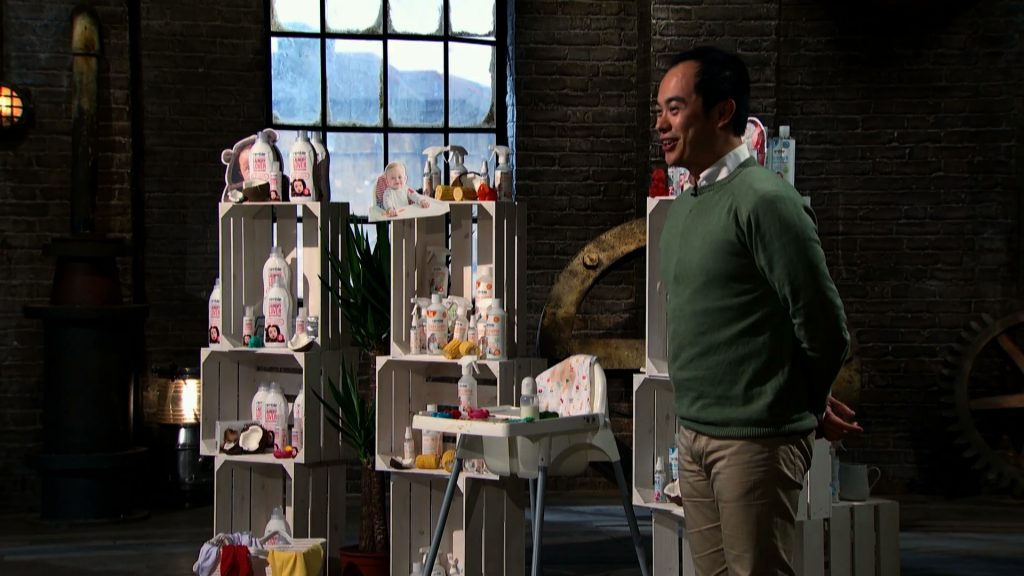 Von Sy smiling in the Den with his range of products displayed behind him